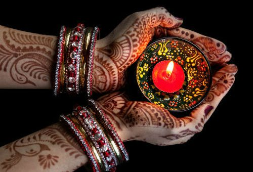 henna hands holding tea light on diwali